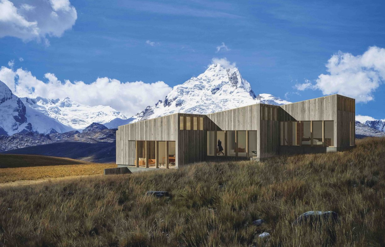 House clad in natural colour, vertical timber panels, located on a sloping grassy landscape with snow-capped mountains in the background.