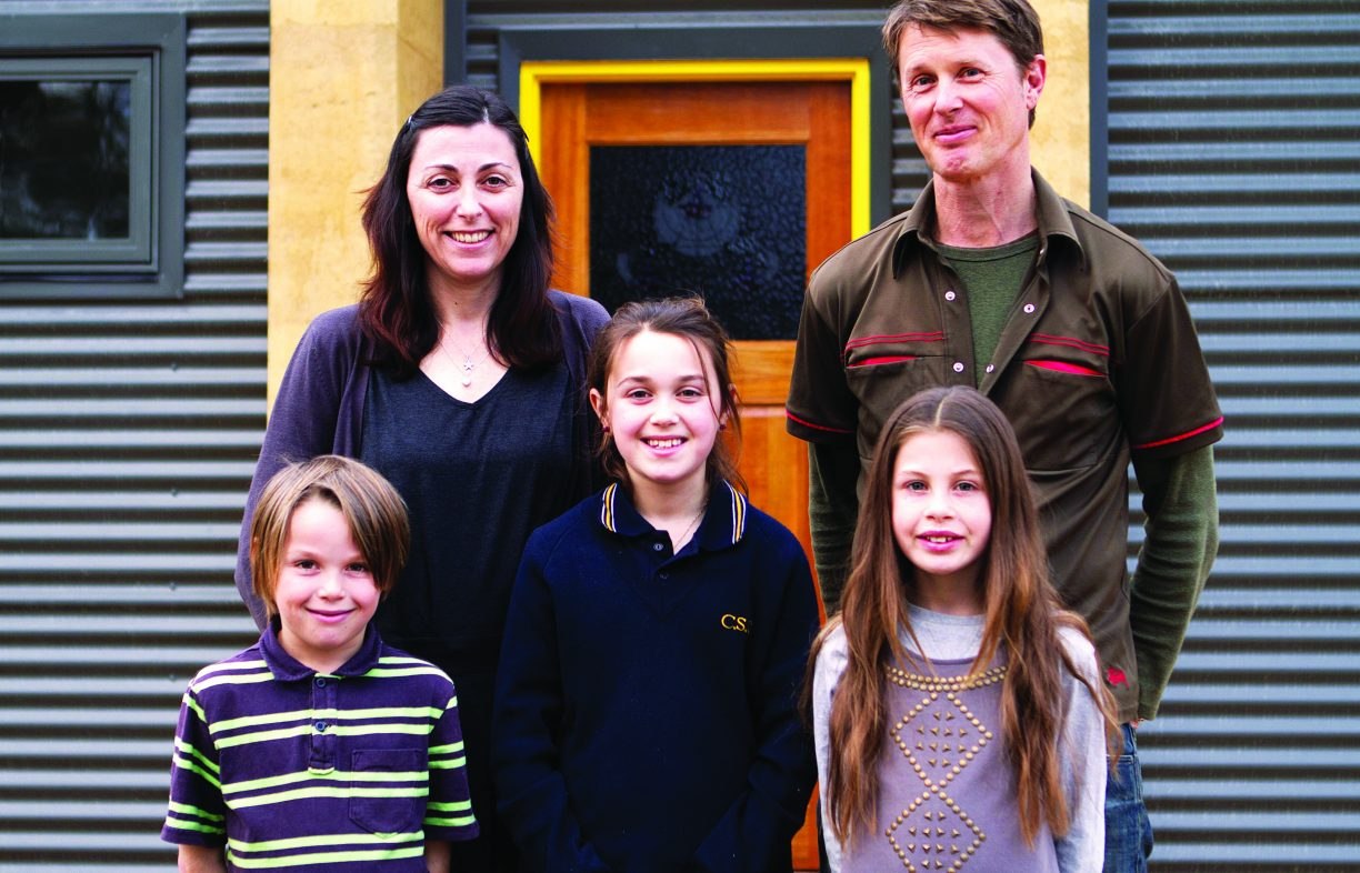 A dark haired woman and auburn haired man stand in front of house with three children, two girls and a boy.