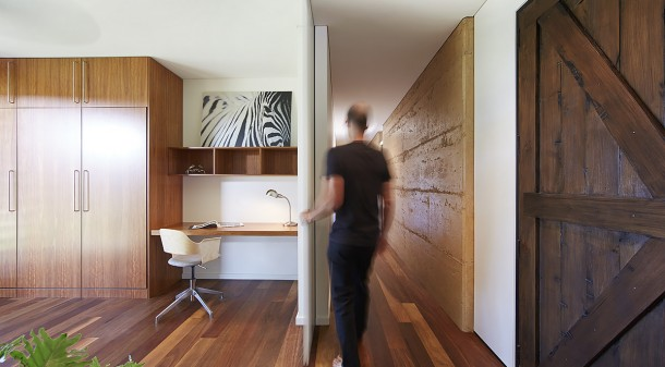 The rammed earth wall stretches through the house and works in concert with concrete floors in the living area to provide thermal mass.