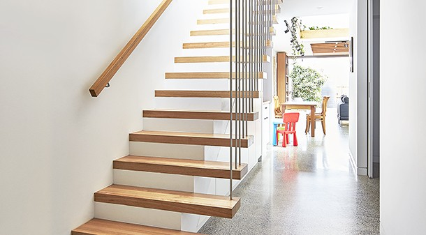 The open design of the staircase lets it function as a light well. Built-in storage is tucked neatly under the stairs.