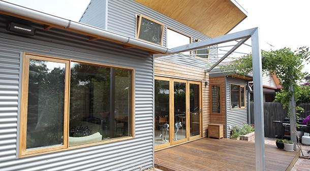 Using tried and true passive solar design features, the north-facing double-glazed windows and doors are shaded in summer by eaves and deciduous climbers, but angled to allow winter sun to penetrate and heat the slab and rammed earth wall.