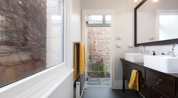 Created by dividing a bedroom in the original house, the ensuite features a vanity made from a repurposed antique sideboard. A glazed shower overlooks a private courtyard between the old house and the new.
