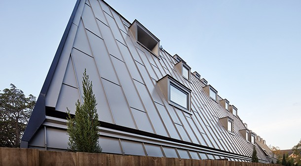 Artisan Apartments' distinctive, gently sloping south-west facade is clad in metal standing seam. These windows are small to reduce unwanted heat loss, but nonetheless provide natural light and ventilation to the apartments.