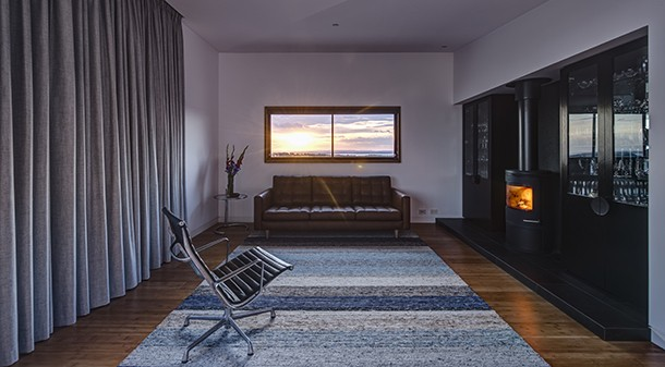 The south-facing, open-plan living room has minimal glazing to the west, and extensive glazing to the south for coastal views. Heavy-duty curtains are used in winter to help retain warmth; and walls, ceilings and floors are filled with insulation.