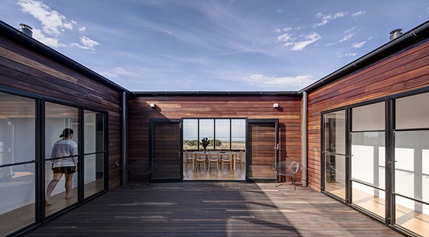 Instead of verandahs, an open-air deck at the heart of the home provides a protected outdoor space and lets natural light into all of the living spaces; the arrangement provides views outwards to the coast and inwards to the connected courtyard.