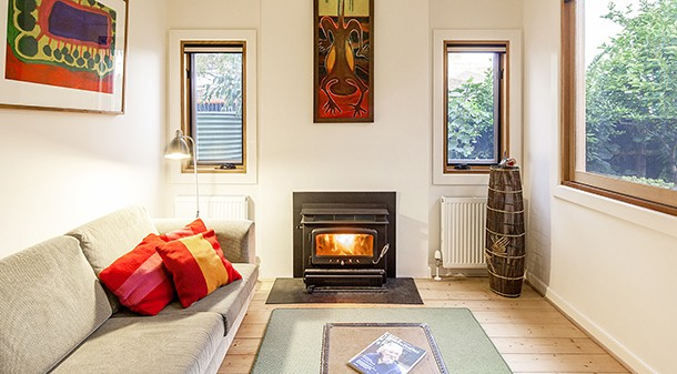 The home's existing living room was rejuvenated with a new window onto the deck and garden and an efficient Nectre wood heater.
