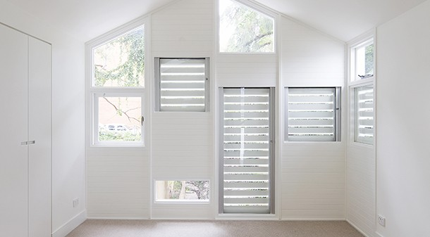 The shutters on these east-facing windows prevent summer overheating of the bedroom, but are easily opened from the inside to allow in winter sunlight.
