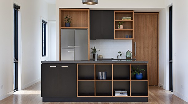 The small kitchen at one end of the home's living space has a spacious pantry tucked behind it and features an Essastone composite stone benchtop, ply and matte black laminex boxes, and blackbutt timber features.
