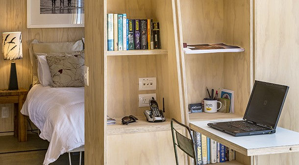 A moveable shelving unit that doubles as a study space separates the bedroom from the rest of the living space. The interior of the house is lined with radiata pine and recycled New Zealand rimu.