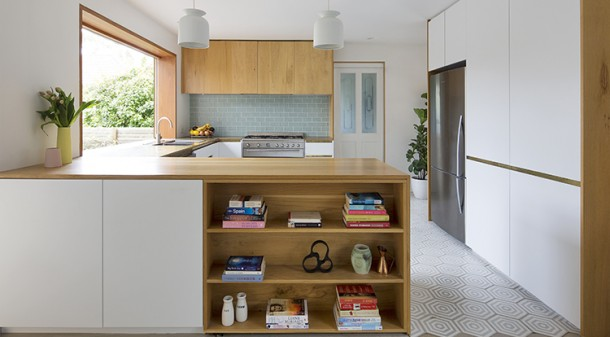 The naturally lit kitchen has benchtops of timber and brass around the sink and stove; tiles for the wall and floor were chosen to match the glass in the original bathroom door.