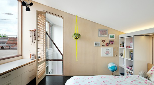 Windows looking across the roof deck and into the void above the living space help make this compact bedroom feel spacious. New FSC-certified plywood with a timber finish complements the recycled materials used for the majority of the renovation.