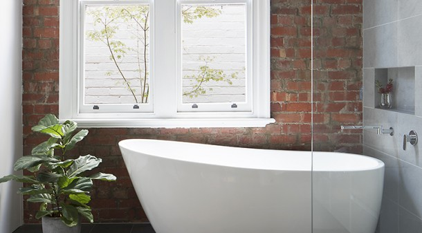 The existing lounge at Curvy House was converted into a generous bathroom and laundry, and the render on the original brick wall was stripped back to make a feature of the brickwork.