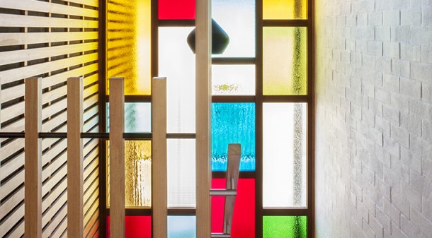 The old blends with the new: Double-glazed stained glass windows mark the connection between the original, bagged brick bungalow and the timber-slatted addition.