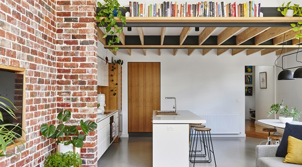 The living room's brick feature wall, rich in thermal mass, was created from the pavers that Leanne and Scott had salvaged from the house's original courtyard. The 40 or more indoor plants are an important part of the interior design strategy.