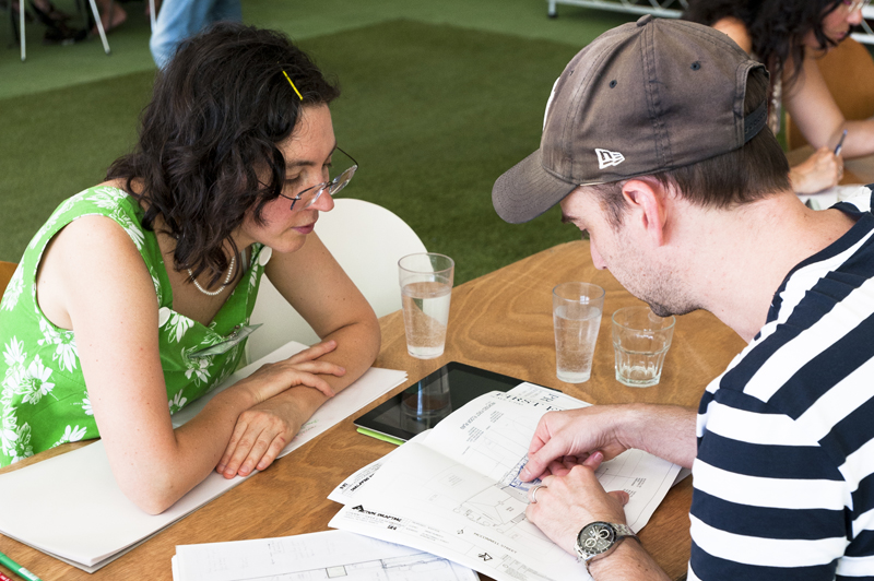 A woman with curly dark hair and in a green shirt and a man in a striped shirt and baseball cap pore over house plans.