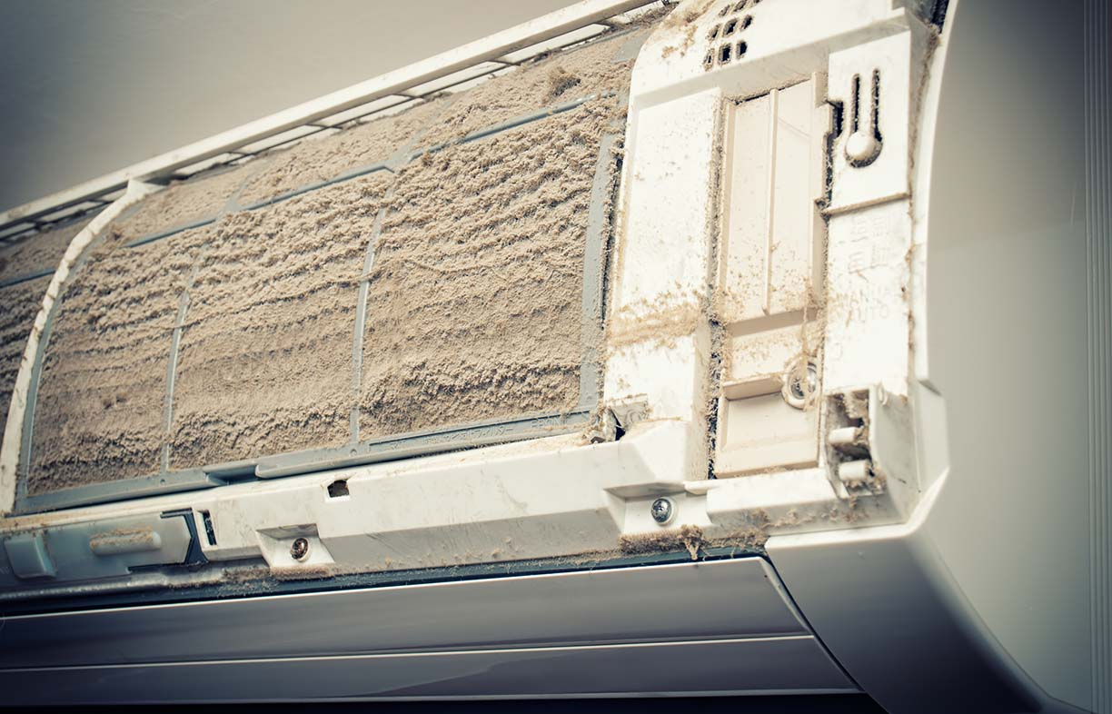 Closeup view of an open Air condition unit and very dirty air filters.