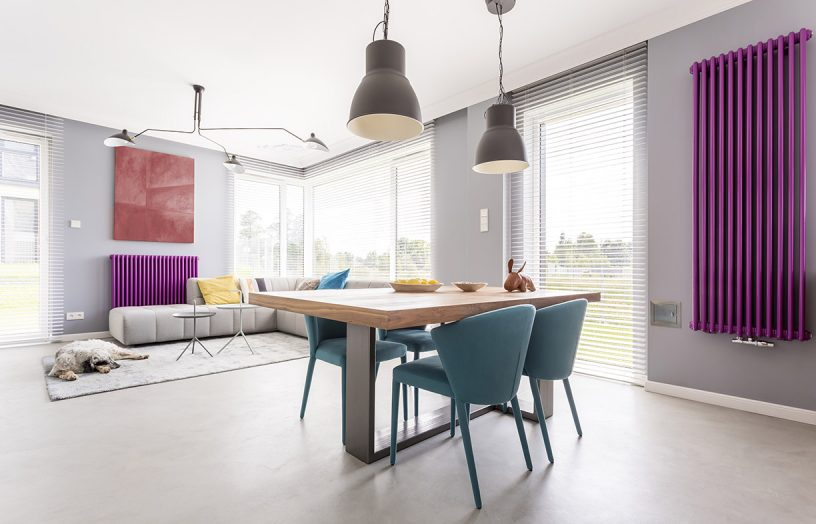 Trendy interior of dining area and open living room with big windows, artwork and colorful accessories