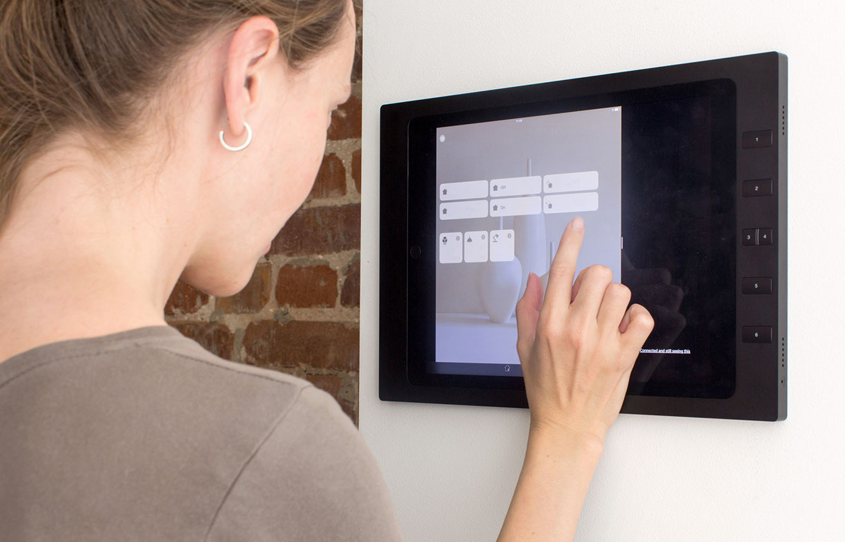 Side view of woman tapping on a tablet built into the wall Smart House