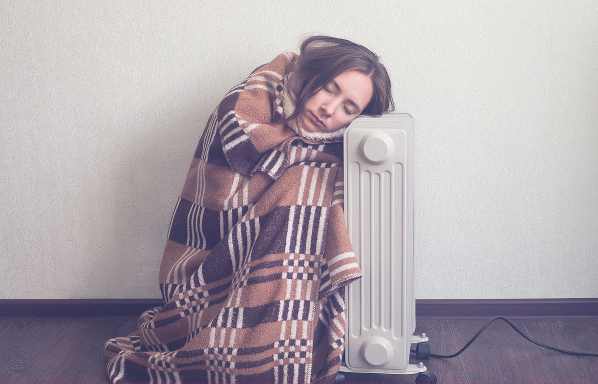 young woman in woolen plaid warm up hands over electric heater