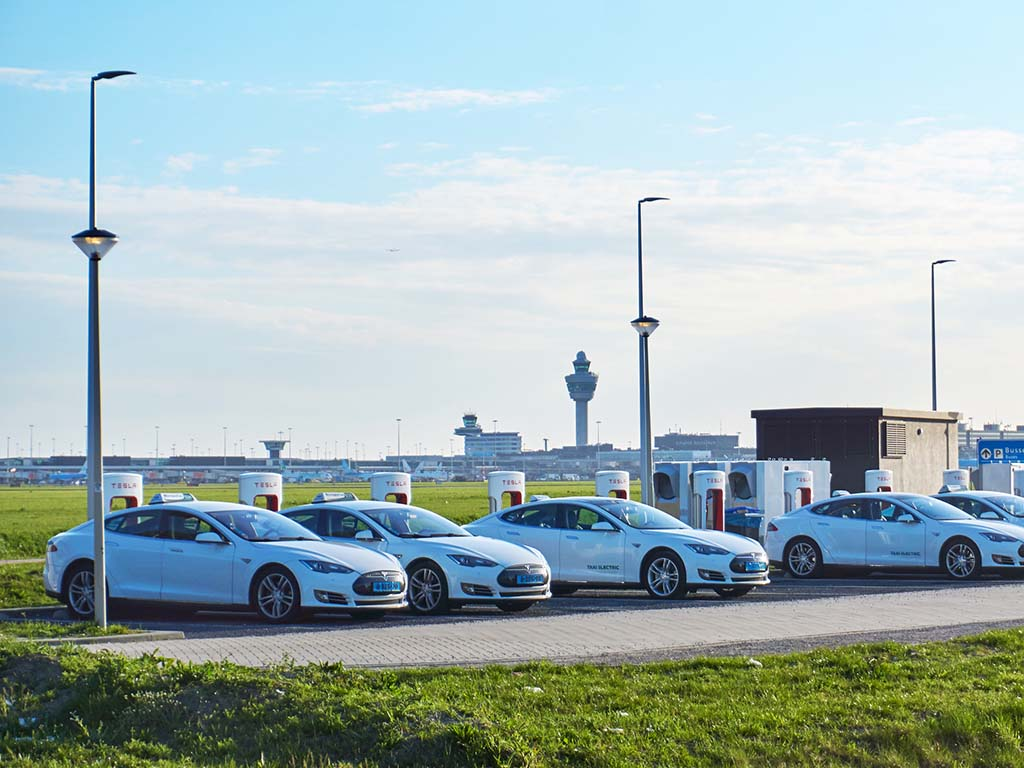 Amsterdam Airport Schiphol, the Netherlands - April 25, 2018: A group of electric vehicle taxis using fast charging infrastructure at airport