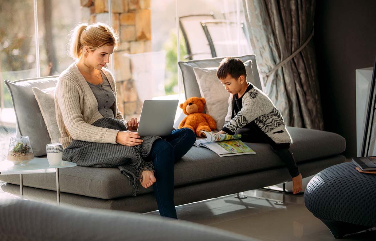 Woman working on laptop with her son reading a storybook. Mother looking busy working on laptop and little boy with a picture book at home.
