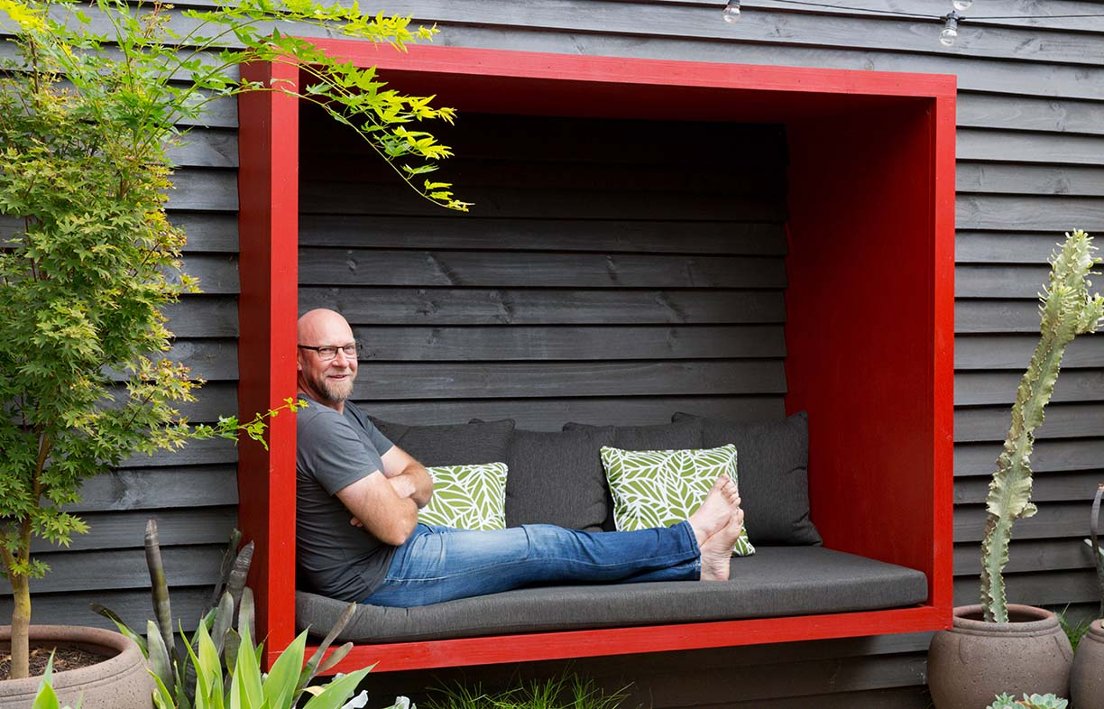 Garden owner and designer Steven Wells, relaxing in a red painted timber seating pod he built, attached to a black painted timber wall.